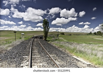 Large fluffy clouds with train track and open farm fields.