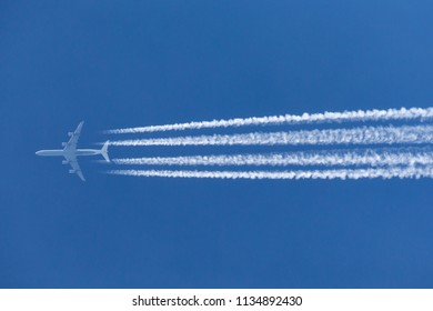 Large four engined commercial airliner jet aircraft flying at high altitude with a large contrail flowing behind it.
