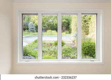Grosses Fenster mit vier Fensterfronten mit Blick auf den Sommerhof mit Pool und Garten