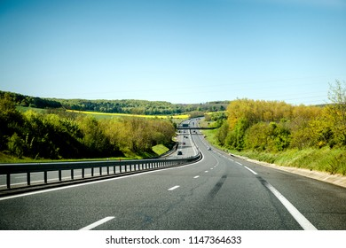 Large French highway perspective view with cars commuting fast on warm spring day with clear sky - driver point of view