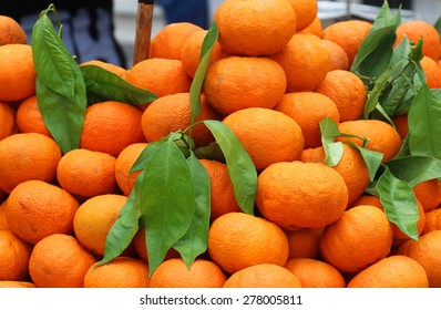 Large fresh tangerines pile with green leaves