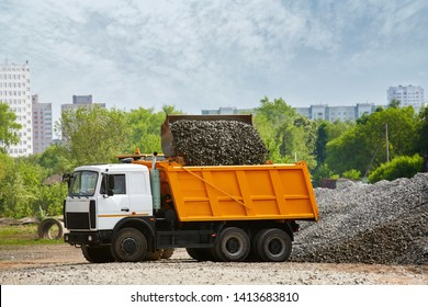 Large front loader loading dumper truck, tipper next to pile of gravel over blue sky. Heavy duty truck loading with rubble and stones. Wheel loader loads a truck with gravel on costruction site.