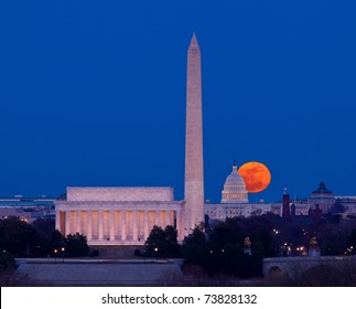 Large full moon rises through the haze over the Capitol building in Washington DC with Lincoln Memorial and Washington Monument aligned