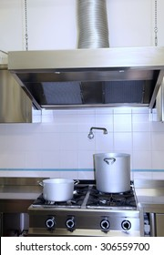 large fume Extractor hood in the industrial kitchen with pots on the stove top