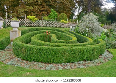 A large garden border with circular topiary hedge in a country house garden