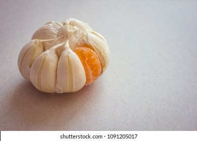 Large garlic onion with one orange slice of mandarin. Strange person, not like the others, odd man out. Hostility, another team. Daylight.