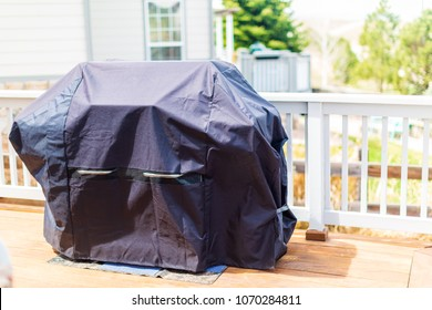 Large gas grill covered with black cover to protect from weather elements.