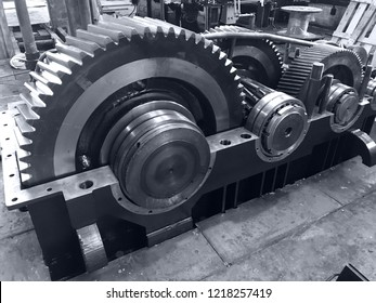 large gearbox open, showing the gears, the whole set attached to a shaft with a cap, industrial environment, photo in black and white with bluish tone