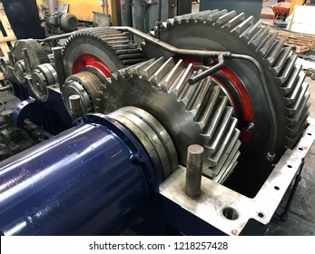 large gearbox open, showing the gears, some painted with a red stripe, the whole set attached to a shaft with blue cap, industrial environment