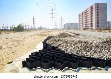 large geogrid at the base of the new road, road construction, reinforcement, on the background of the power station and unfinished house