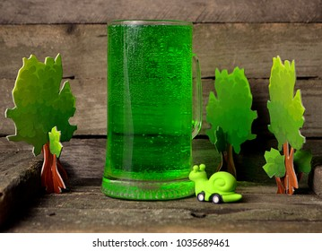 A large glass glass with a green drink on the background of wooden boards with a cochlea figurine made of rubber.
