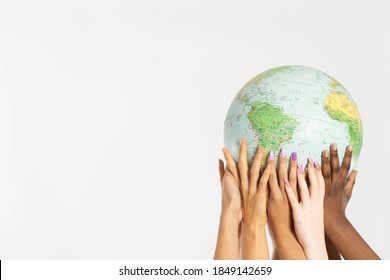 A large globe with all continents is supported by female hands of various races, symbolizing unity, acceptance and racial tolerance.