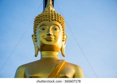 Large golden buddha statue on blue sky