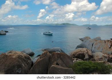 Large granite boulders, lush vegetation and boats at The Baths.  British Virgin Islands.
