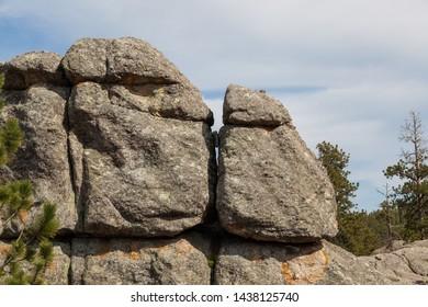 Large granite rock formations and trees along the shoreline of  Sylvan Lake in South Dakota.