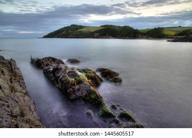 Large granite/slate rock covered in green seaweed. Long exposure used to blur and add drama to the motion of the incoming tide,  Menabilly, Cornwall, England, UK