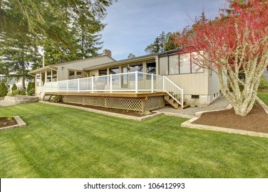 Large grass porch with one story beige house with grass lawn.