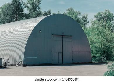 Large gray hangar among the trees