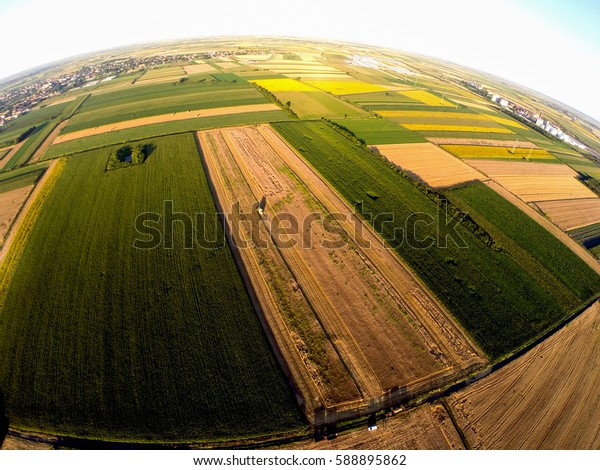 Large green agricultural fields. Landscape through fish eye lens at beautiful sunrise in countryside