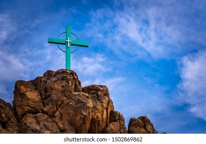 Large green crucifix with a smaller white crucifix in the center.  The crucifix in embedded in a rock formation, shot low against the sky with lots of sky and clouds visible