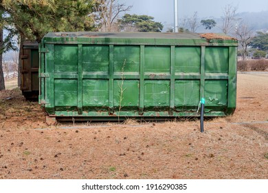 Large green metal trash container in rural public park.