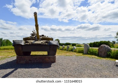 A large green military metal armored deadly dangerous iron Russian Syrian battle tank with a gun turret and a goose is parked parked against a blue sky and clouds outside the city.