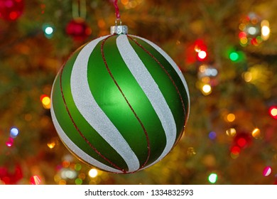 large green and white and red christmas tree ornament with defocussed tree and lights behind it