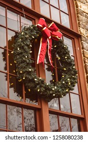 A large green wreath with with lights on a glass window in a stone wall.