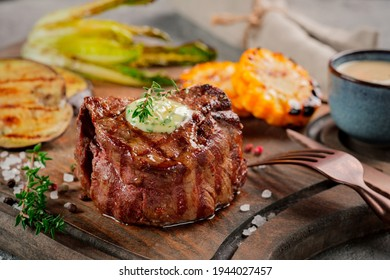 Large grilled Filet Mignon steak with butter and thyme served on a wooden board. Grilled meat dish with vegetables
