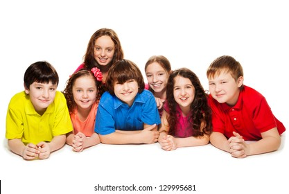 Large group of boys and girls laying on the floor together, smiling and happy, isolated on white