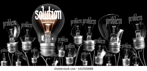 Large group of broken and shining light bulbs with fibers in a shape of Problem and Solution isolated on black background