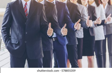 Large group of business people showing thumbs up.,fine portrait of team leader young businessman showing thumbs up,business and finance,Start up Young Asian Business team hope to success