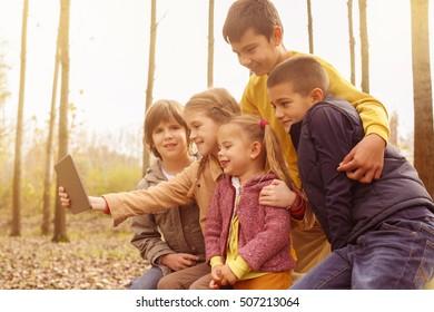 Large group of cheerful children enjoy digital tablet.