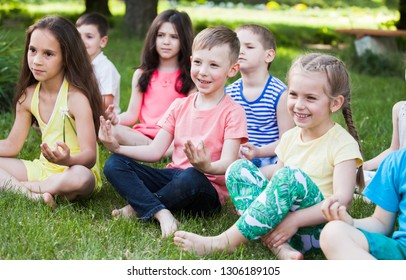 A large group of children engaged in yoga in the Park sitting on the grass