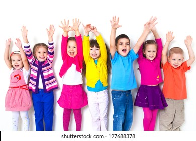 large group of children happily pulled his hands up in  white wall