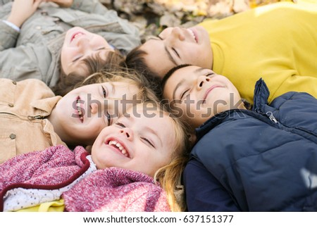 Large group of children. Happy children lying on falling leaves.