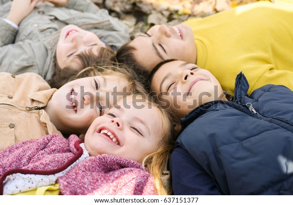 Un grande gruppo di bambini. Bambini felici sdraiati su foglie cadenti.