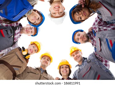 Large group of construction workers standing in circle. Isolated on white