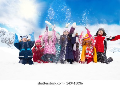 Large group of diversity looking kids boys and girls throwing snow in the air together