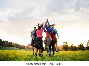 Large group of fit and active people jumping after doing exercise in nature.