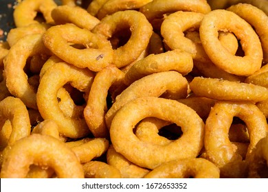 Large group of freshly fried calamari and onion rings on display for sale at a street food festival, ready to eat healthy seafood, beautiful orange monochrome outdoor background