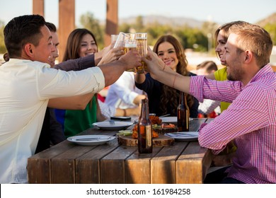 Large group of friends making a toast with beer while hanging out at a restaurant