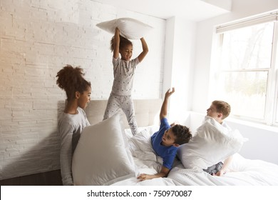 A large group of friends taking goog time on bed with pillow fight