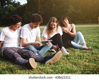 large group of friends together in a park studying with digital tablets, back to school