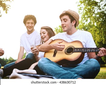 large group of friends together in a park having fun playing music