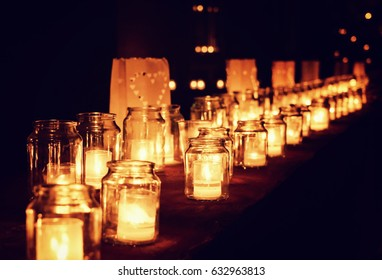Large group of glass jars with burning candles on the dark background, selective focus. Hygge concept
