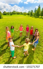 Large group of happy girls play roundelay and stand in circle in the park on the green grass on sunny summer day, view from above