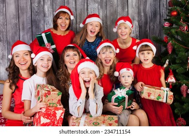 Large Group of happy people in Christmas hat with presents