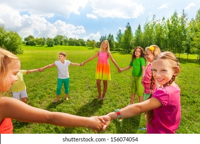 Large group of happy smiling and dancing girls play roundelay and stand in circle in the park on the green grass on sunny summer day