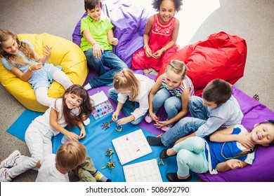 Large Group of happy smiling kids sitting together and playing indoor